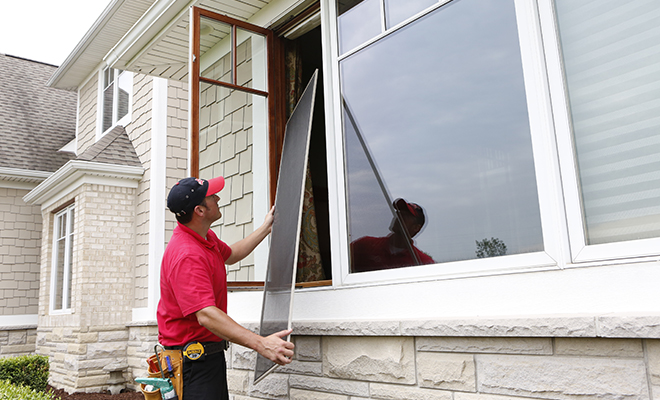 Mr Handyman technician installing a window screen