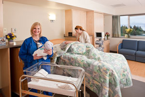 nurse holding baby in hospital room