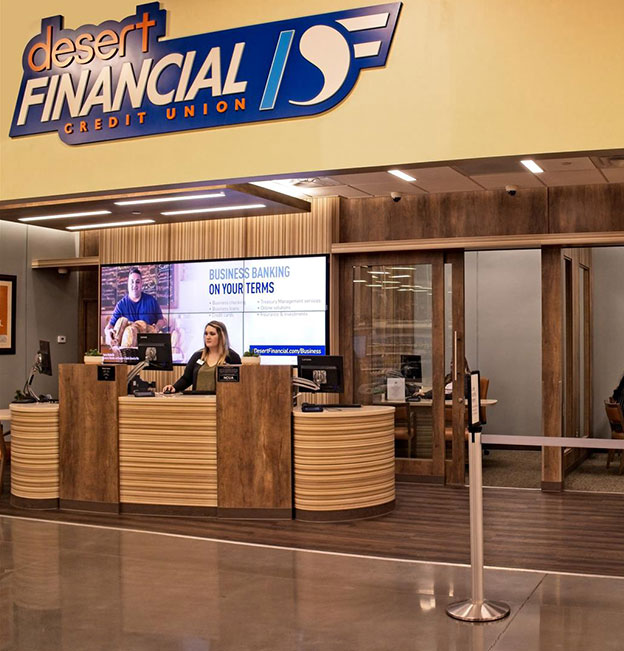 woman standing behind desert financial branded service desk