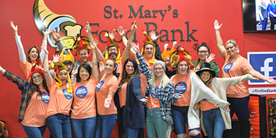 group celebrating in front of St. Mary's food bank sign