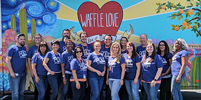 group standing in front of a waffle love sign