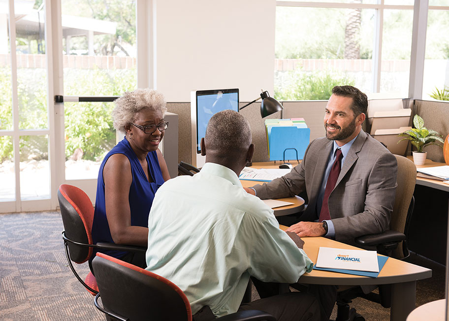 financial planner talking to a couple in a branch setting