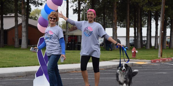 Employees walking a dog in a Relay for Life